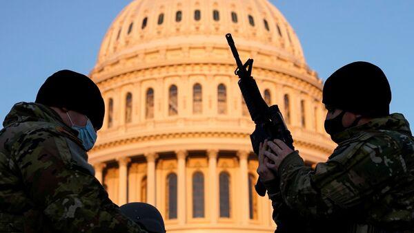 Một thành viên của Lực lượng Vệ binh Quốc gia Hoa Kỳ nhận vũ khí bên ngoài tòa nhà Capitol ở Washington DC - Sputnik Việt Nam