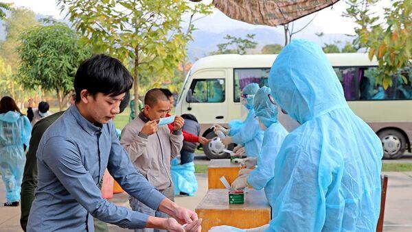 Công dân về từ Pháp rửa tay sát khuẩn tại khu cách ly tập trung. - Sputnik Việt Nam