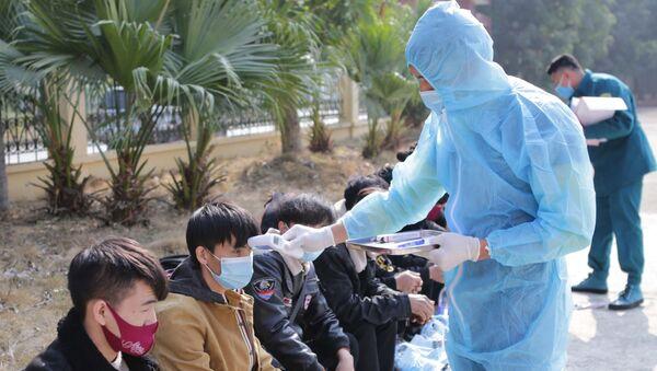 Kiểm tra y tế các trường hợp vượt biên trái phép chuẩn bị được đưa đi cách ly nhằm đảm bảo không có sự lây lan dịch bệnh tại khu cách ly cửa khẩu Ma Lù Thàng. - Sputnik Việt Nam