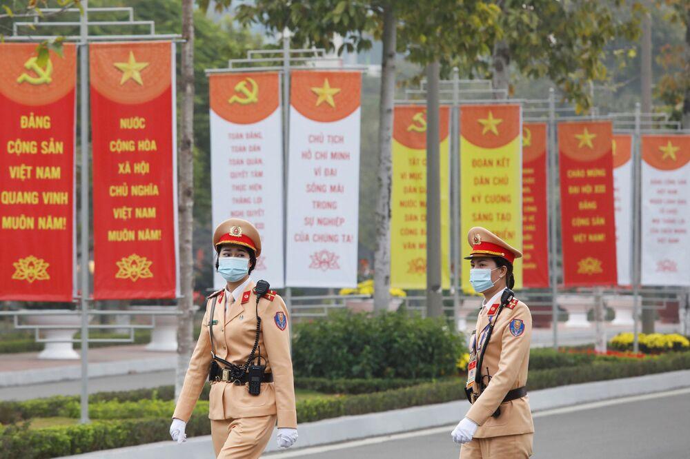 Nữ nhân viên cảnh sát ngang qua biển hiệu tại Trung tâm Hội nghị Quốc gia, nơi diễn ra Đại hội lần thứ XIII của Đảng Cộng sản Việt Nam