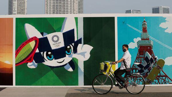 Một người đàn ông đi xe đạp lướt qua bức vẽ graffiti về chủ đề Thế vận hội Olympic ở Nhật Bản - Sputnik Việt Nam