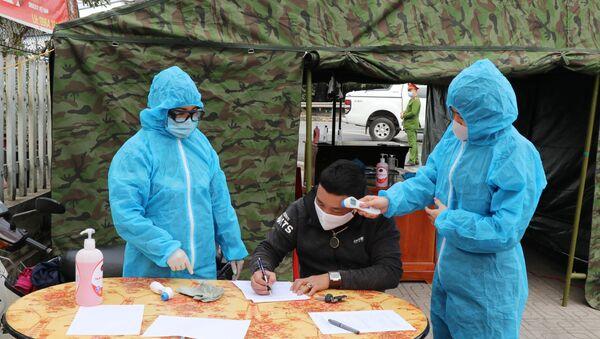 Nhân viên y tế hướng dẫn lái xe ngoại tỉnh khai báo y tế và kiểm tra thân nhiệt tại chốt kiểm tra liên ngành nút giao Thịnh Đán, Thành phố Thái Nguyên  - Sputnik Việt Nam