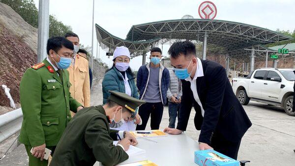 Lực lượng chức năng làm nhiệm vụ ở chốt kiểm dịch COVID-19 đặt tại trạm thu phí cao tốc Hạ Long - Vân Đồn, thuộc địa phận huyện Vân Đồn. - Sputnik Việt Nam
