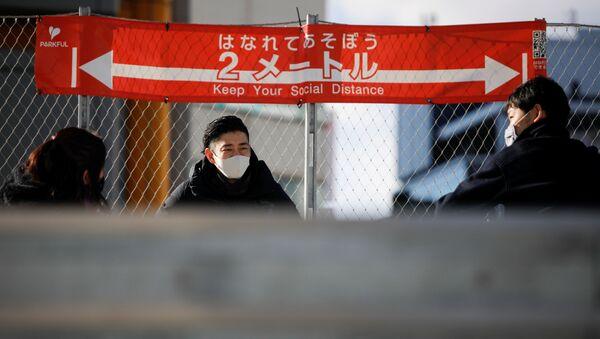 Những người đeo khẩu trang trên nền tấm áp phích yêu cầu tuân thủ giãn cách xã hội ở Tokyo. - Sputnik Việt Nam