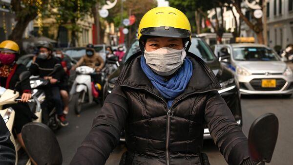 Người phụ nữ đeo khẩu trang ở Hà Nội. - Sputnik Việt Nam