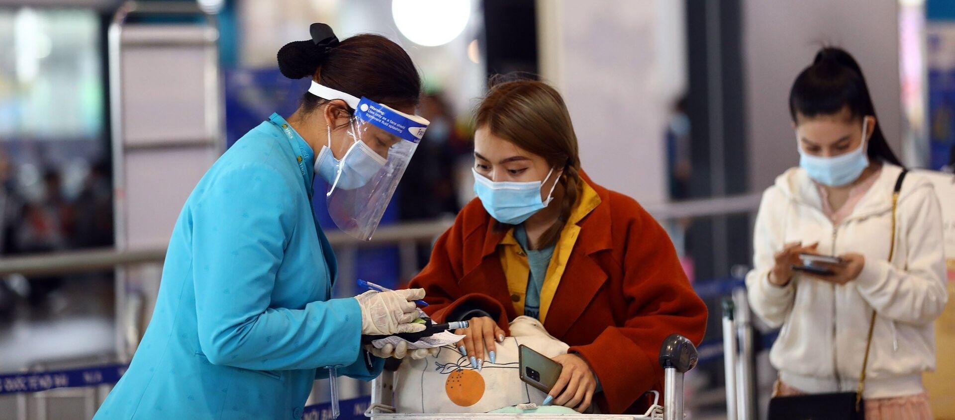 Nhân viên của hãng hàng không Vietnam Airlines đeo đầy đủ khẩu trang, mặt nạ chống giọt bắn để đảm bảo phòng chống dịch Covid-19.  - Sputnik Việt Nam, 1920, 08.02.2021