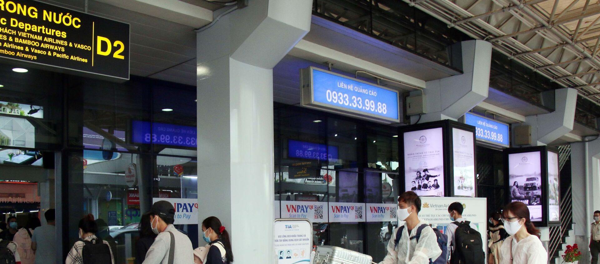 Để phòng chống dịch, nhiều hành khách đã chủ động trang bị các bộ đồ bảo hộ khi đến sân bay Tân Sơn Nhất. - Sputnik Việt Nam, 1920, 11.03.2021