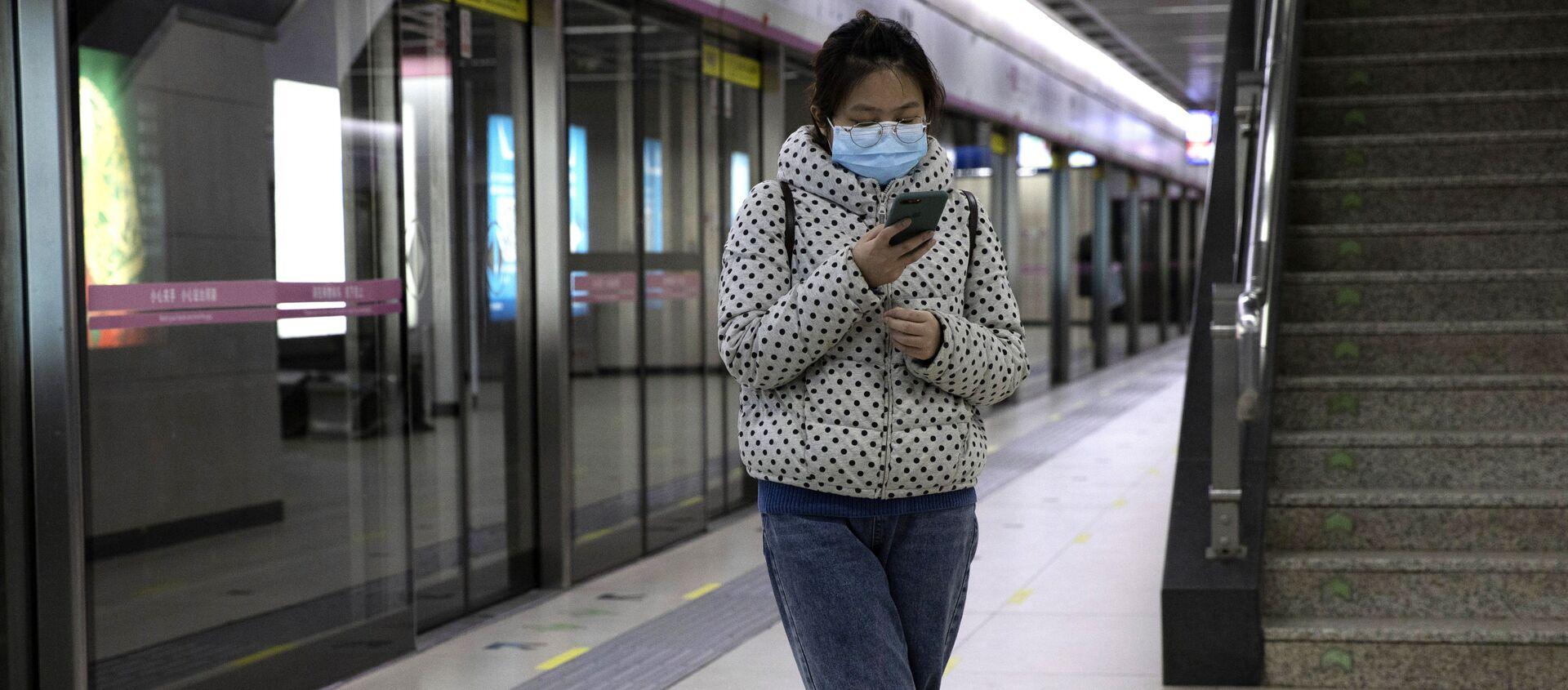 Cô gái với chiếc điện thoại thông minh ở ga tàu điện ngầm Vũ Hán. - Sputnik Việt Nam, 1920, 10.02.2021