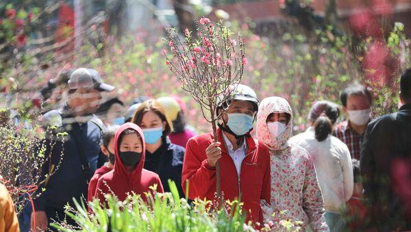 Người dân đi chợ hoa Tết truyền thống trong ngày 29 Tết đều thực hiện nghiêm túc việc đeo khẩu trang để phòng chống dịch. - Sputnik Việt Nam