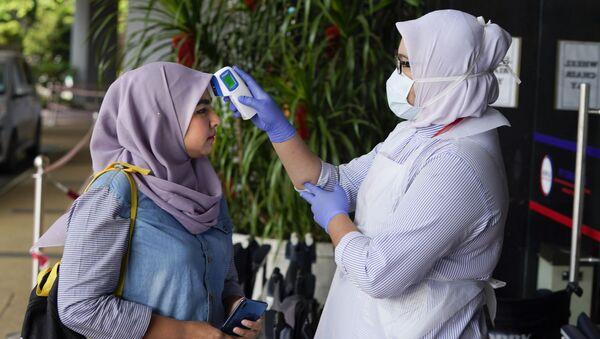 Một y tá trong bệnh viện đo nhiệt độ cho một công dân Malaysia - Sputnik Việt Nam