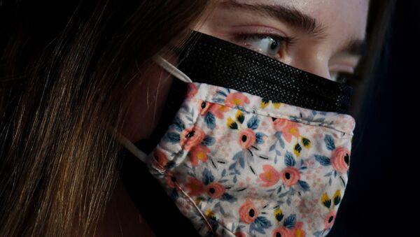 Cô gái đeo chiếc hai khẩu trang che mặt, khẩu trang vải bên ngoài, khẩu trang y tế bên trong, ở Arlington, Virginia, Hoa Kỳ. - Sputnik Việt Nam