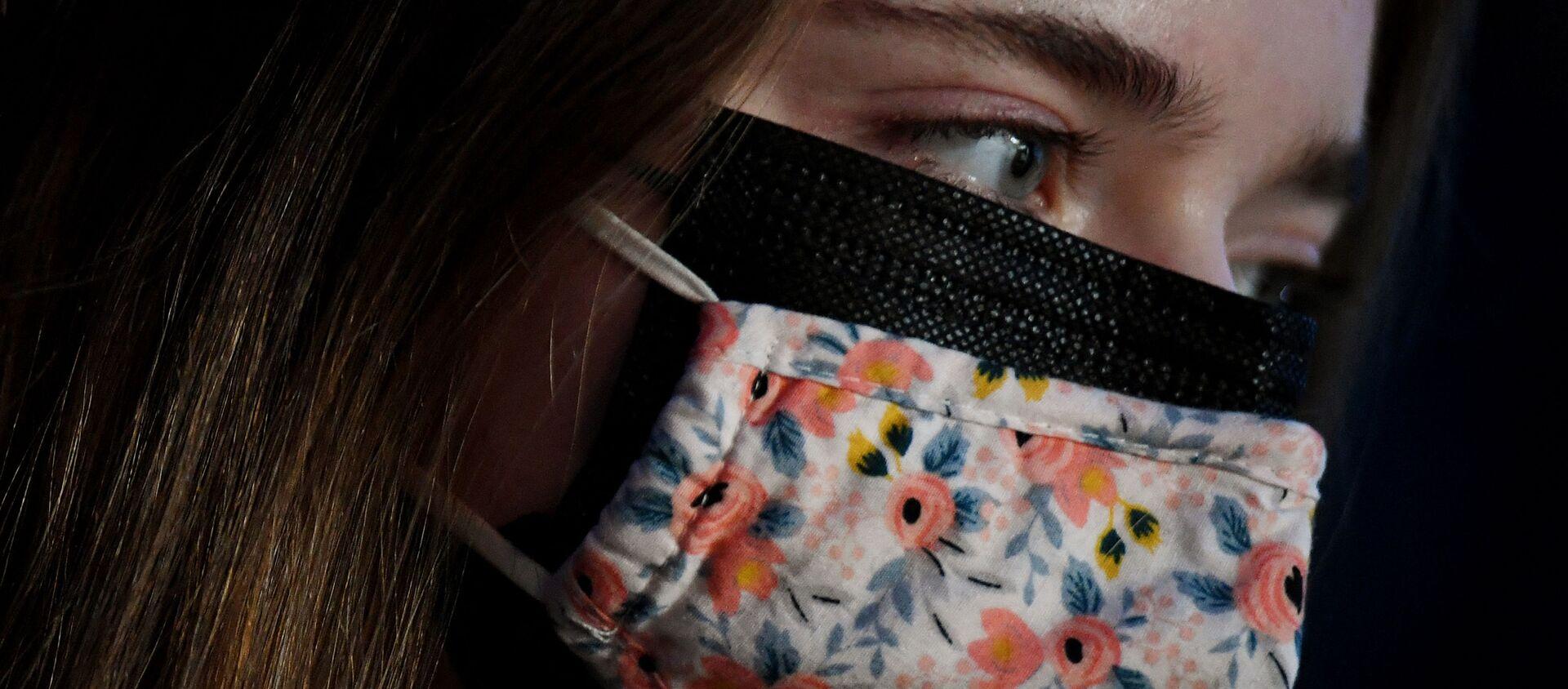 Cô gái đeo chiếc hai khẩu trang che mặt, khẩu trang vải bên ngoài, khẩu trang y tế bên trong, ở Arlington, Virginia, Hoa Kỳ. - Sputnik Việt Nam, 1920, 14.02.2021