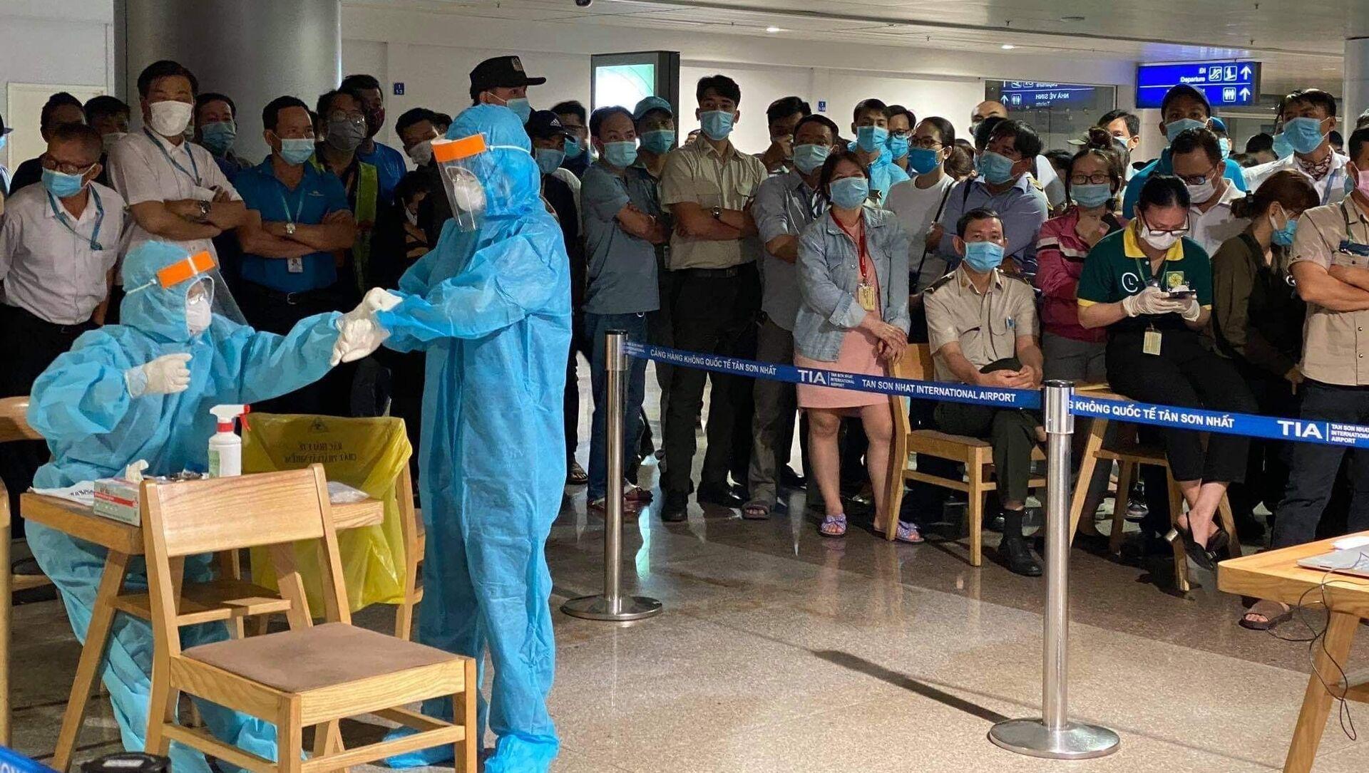 Nhân viên y tế làm thủ tục lấy mẫu xét nghiệm cho người làm việc tại sân bay Tân Sơn Nhất, ngày 6/2. - Sputnik Việt Nam, 1920, 30.03.2021