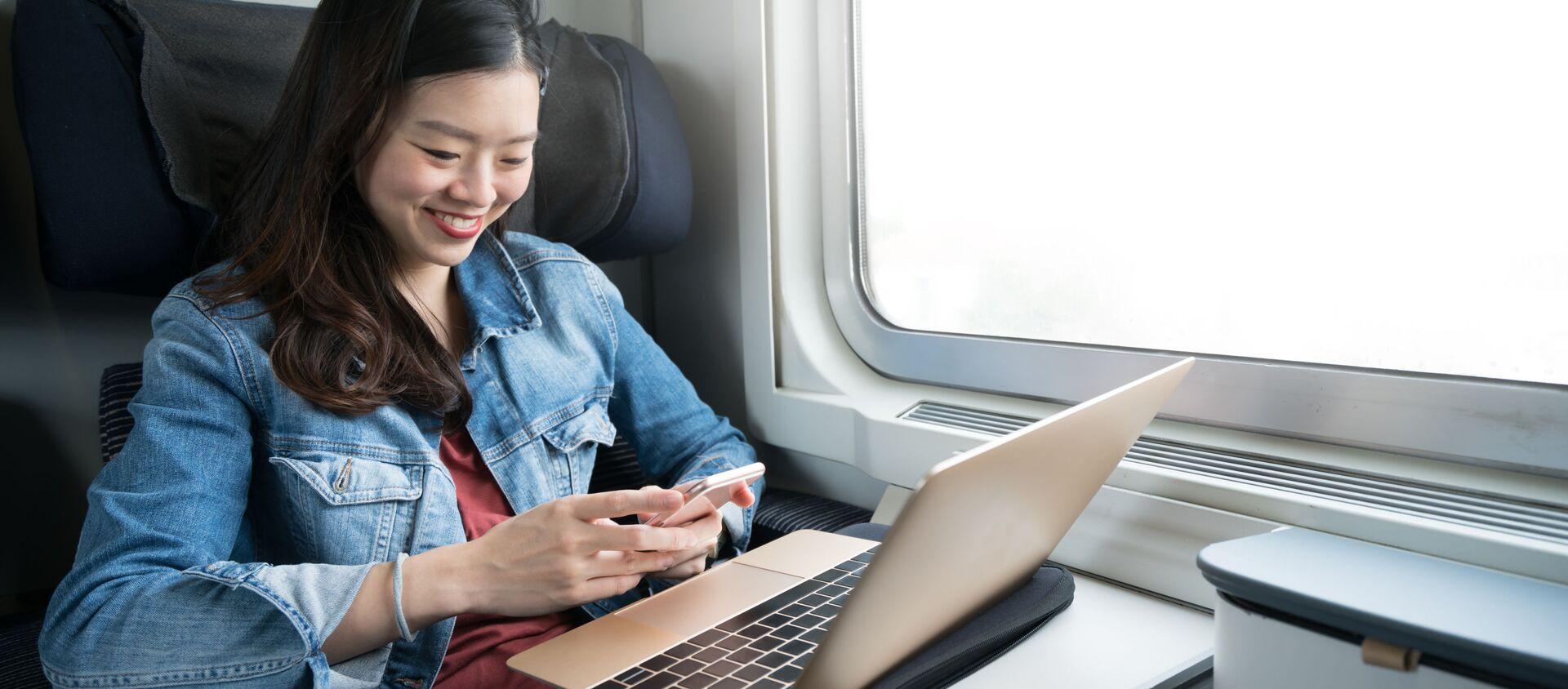 Cô gái đi trên tàu với máy tính xách tay và điện thoại - Sputnik Việt Nam, 1920, 23.02.2021