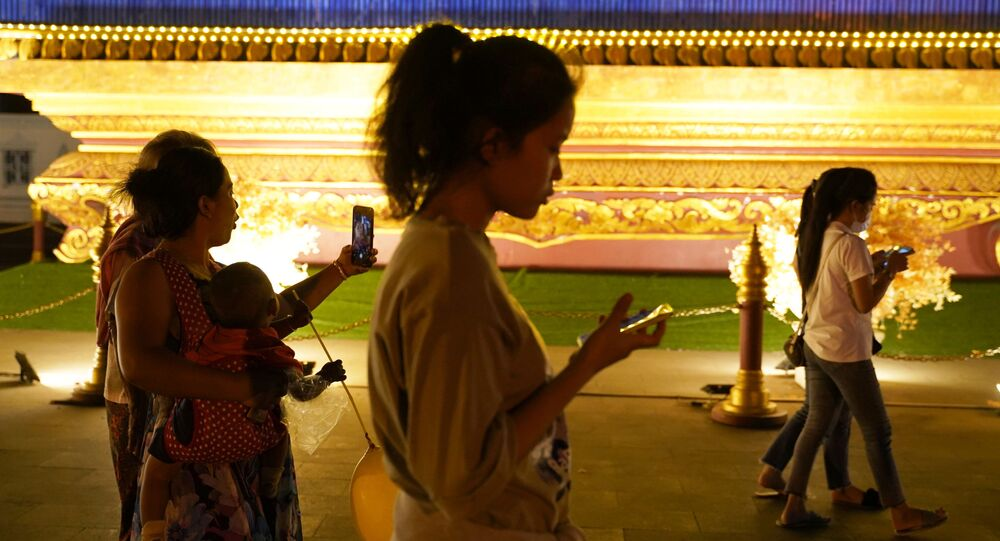 Khách bộ hành cầm điện thoại di động, Phnom Penh, Campuchia.