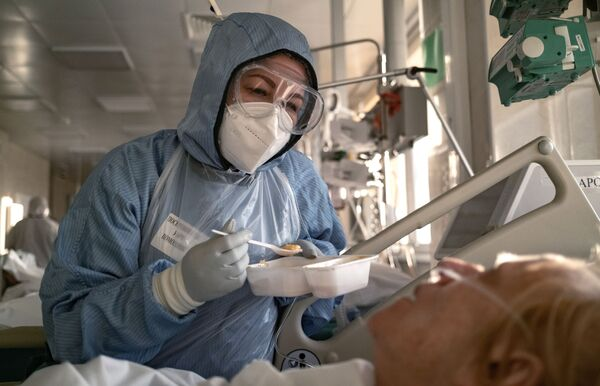 Nữ y tá cho bệnh nhân ăn trong phòng chăm sóc đặc biệt tại bệnh viện ở Moskva - Sputnik Việt Nam