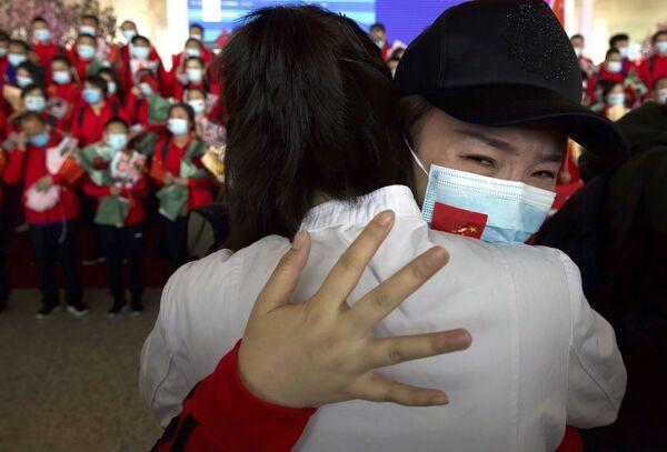 Nữ nhân viên y tế tỉnh Cát Lâm, Trung Quốc tạm biệt các đồng nghiệp tại sân bay quốc tế Thiên Hà, Vũ Hán, Trung Quốc - Sputnik Việt Nam