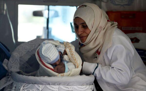 Nữ y tá với cặp song sinh trong xe cấp cứu tại sân bay Sana'a, Yemen - Sputnik Việt Nam