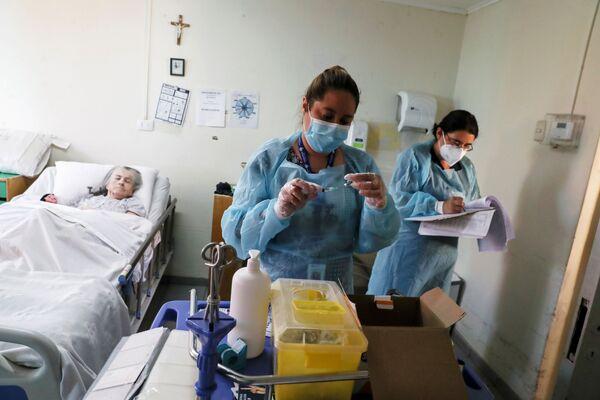 Các nữ nhân viên y tế tại viện dưỡng lão ở Santiago trước khi tiêm vắc xin chống coronavirus cho nữ bệnh nhân lớn tuổi - Sputnik Việt Nam