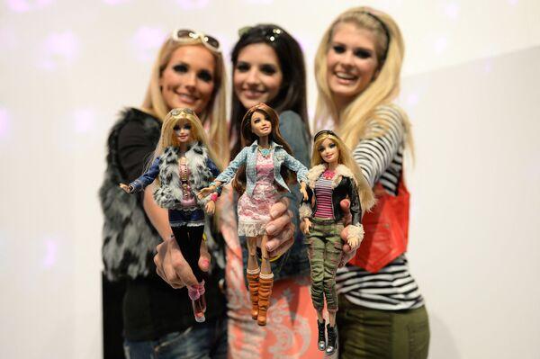Những người mẫu tạo dáng với búp bê Barbie mặc trang phục tương tự, tại quầy Mattel trong Triển lãm đồ chơi quốc tế ở Nieders - Sputnik Việt Nam
