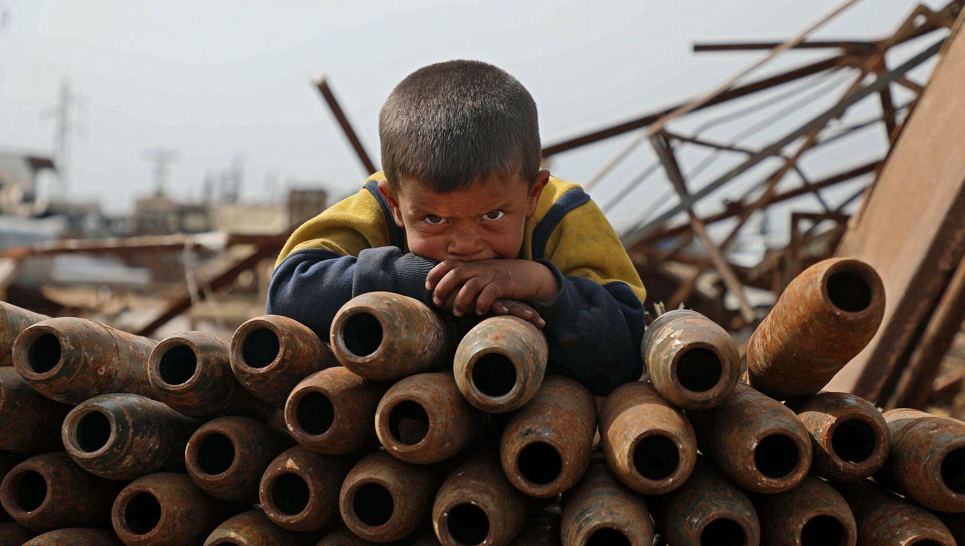 Đứa trẻ bên đống vỏ đạn trong bãi phế liệu ở thành phố Maaret-Misrin, tỉnh Idlib, Syria - Sputnik Việt Nam, 1920, 18.03.2021