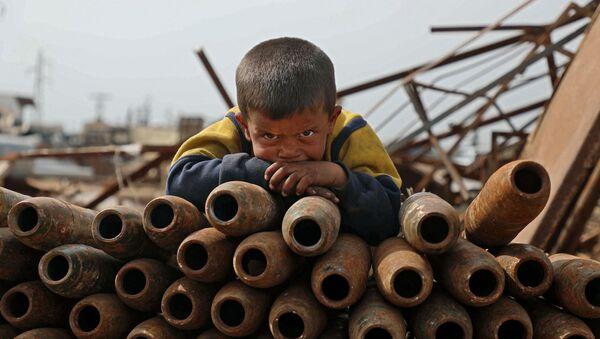Đứa trẻ bên đống vỏ đạn trong bãi phế liệu ở thành phố Maaret-Misrin, tỉnh Idlib, Syria - Sputnik Việt Nam