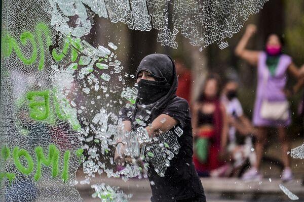 Người phụ nữ đập vỡ kính trong cuộc biểu tình nhân Ngày Quốc tế Phụ nữ ở Mexico City, Mexico - Sputnik Việt Nam