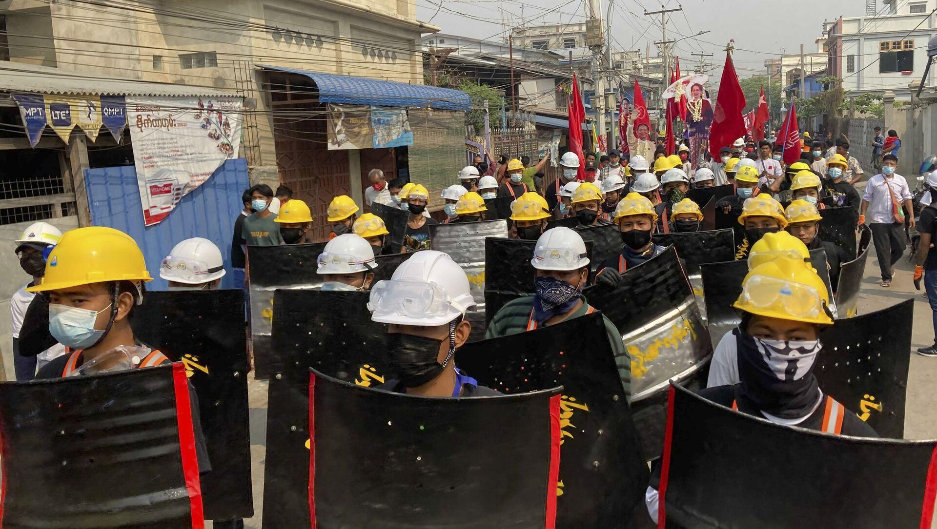 Người biểu tình tuần hành với những tấm chắn tạm bợ trên một con đường chính trong cuộc biểu tình ở Mandalay, Myanmar, Thứ Hai, ngày 8 tháng 3 năm 2021. Các cuộc biểu tình lớn đã xảy ra hàng ngày trên nhiều thành phố và thị trấn ở Myanmar. - Sputnik Việt Nam, 1920, 12.03.2021