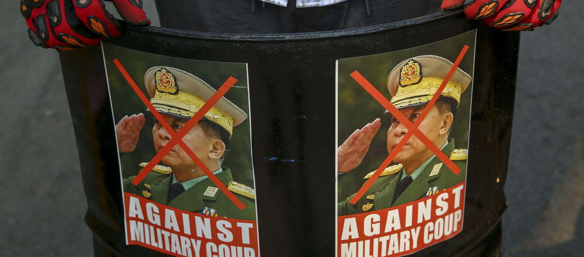 Một người biểu tình chống đảo chính trưng bày những hình ảnh bị bôi nhọ của Tổng tư lệnh, Thượng tướng Min Aung Hlaing ở Mandalay, Myanmar, Thứ Tư, ngày 3 tháng 3 năm 2021. - Sputnik Việt Nam, 1920, 16.03.2021