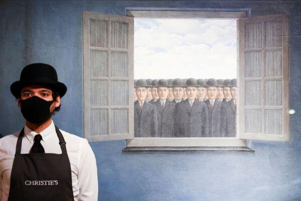 Một trợ lý phòng trưng bày tạo dáng bên cạnh tác phẩm Le Mois des Vendanges của nghệ sĩ René Magritte trong một buổi chụp ảnh tại Christie's ở London - Sputnik Việt Nam