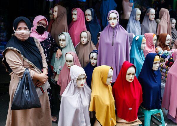 Những người phụ nữ đeo khẩu trang đứng cạnh những chiếc khăn trùm đầu được bày bán tại chợ dệt may Tanah Abang ở Jakarta, Indonesia. - Sputnik Việt Nam