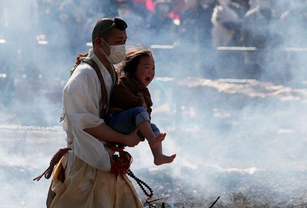 Nhà sư Phật giáo bế một đứa trẻ đang khóc trong lễ hội đi bộ trên lửa ở Nhật Bản - Sputnik Việt Nam