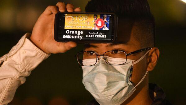 Một người đàn ông cầm điện thoại với thông điệp về tội ác căm thù đối với người Mỹ gốc Á trong một cuộc đấu trí ở Fountain Valley, California - Sputnik Việt Nam