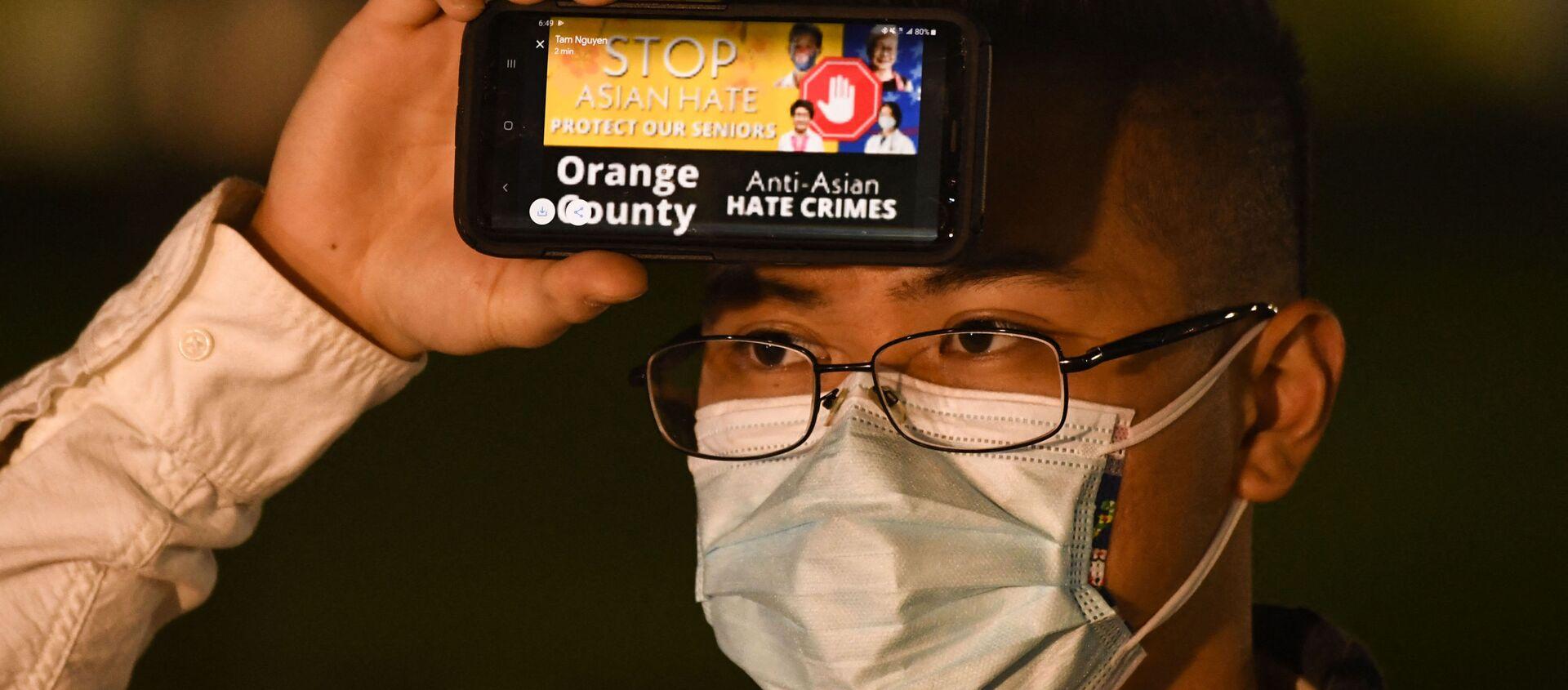 Một người đàn ông cầm điện thoại với thông điệp về tội ác căm thù đối với người Mỹ gốc Á trong một cuộc đấu trí ở Fountain Valley, California - Sputnik Việt Nam, 1920, 19.03.2021