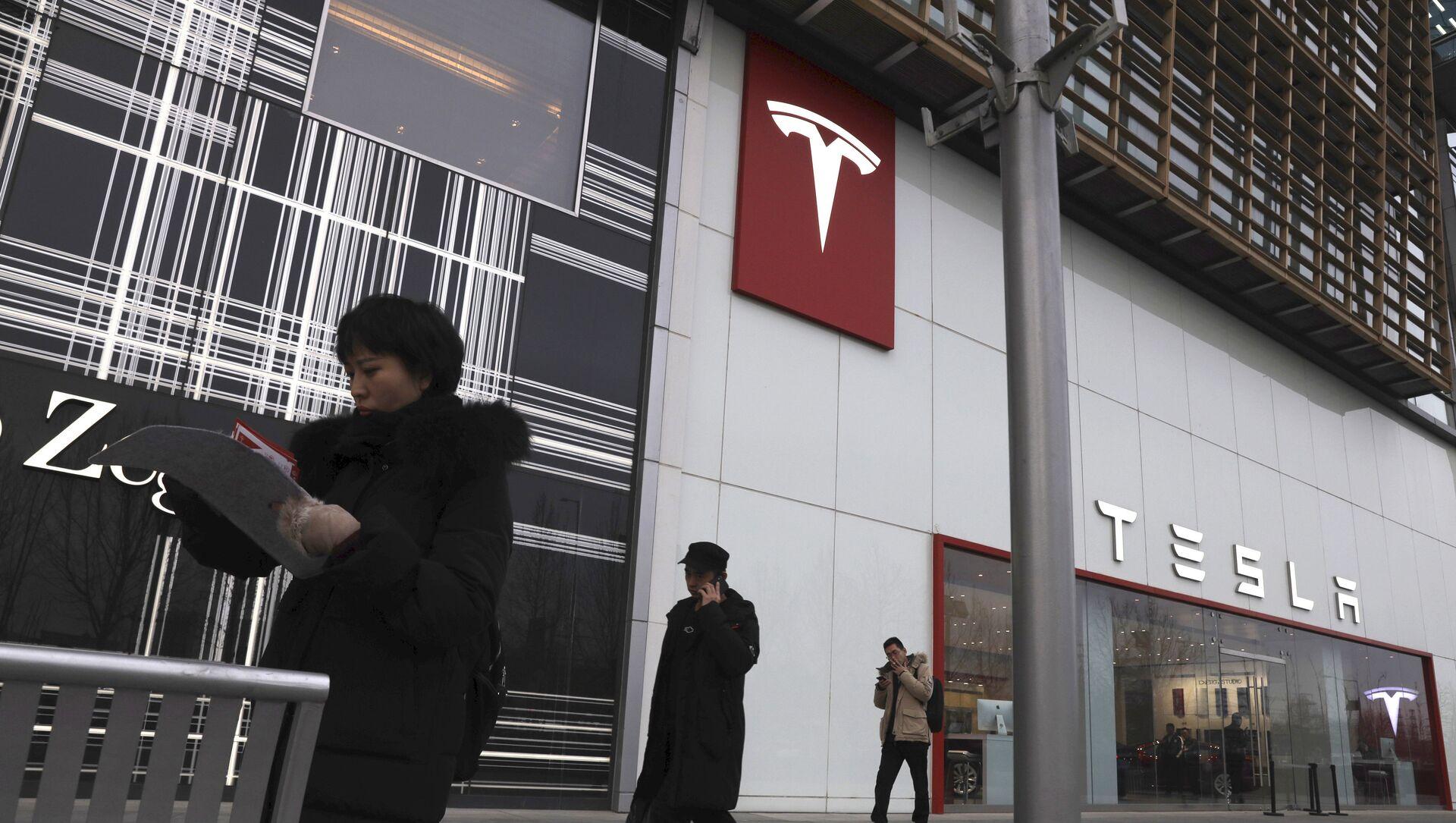 Residents walk past a Tesla store in Beijing - Sputnik Việt Nam, 1920, 03.07.2021