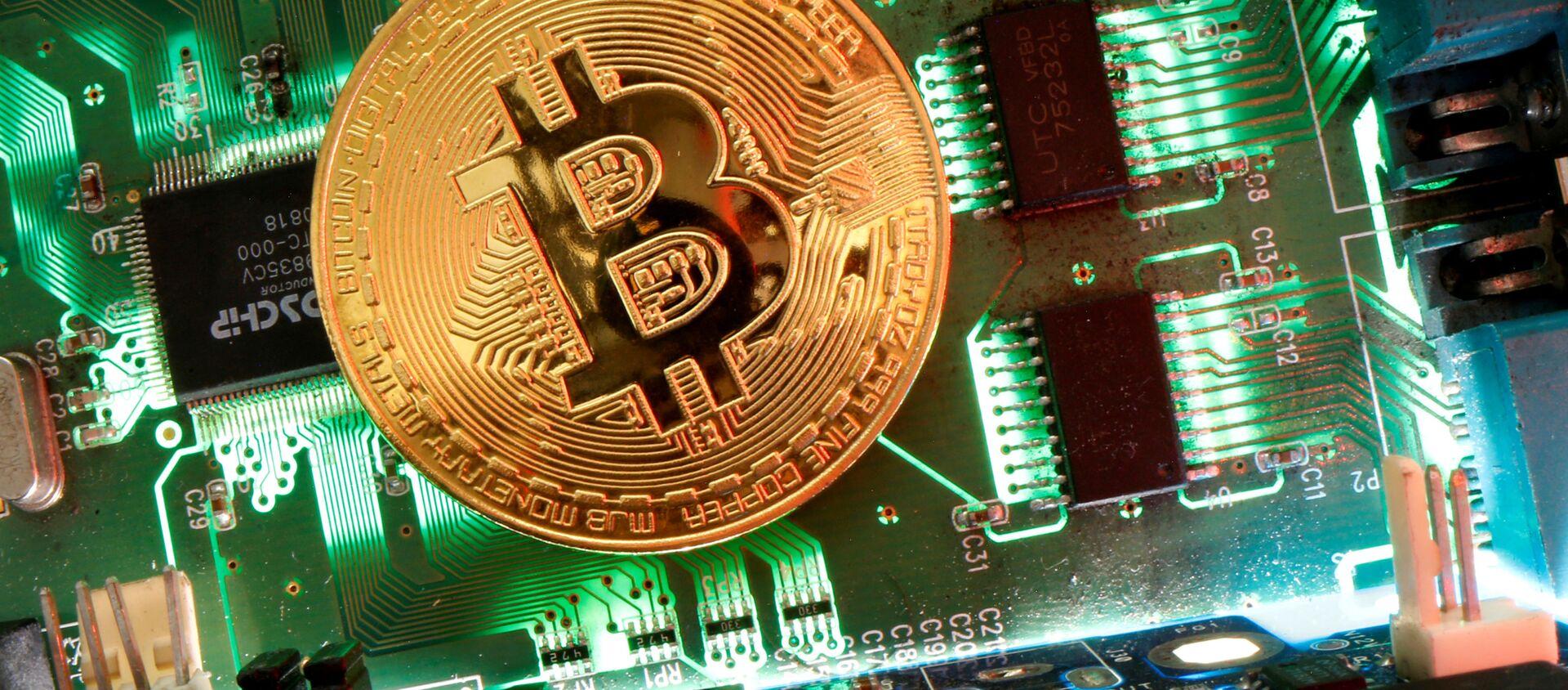 Đại diện của tiền ảo Bitcoin được nhìn thấy trên bo mạch chủ trong hình minh họa này được chụp vào ngày 24 tháng 4 năm 2020 - Sputnik Việt Nam, 1920, 21.03.2021