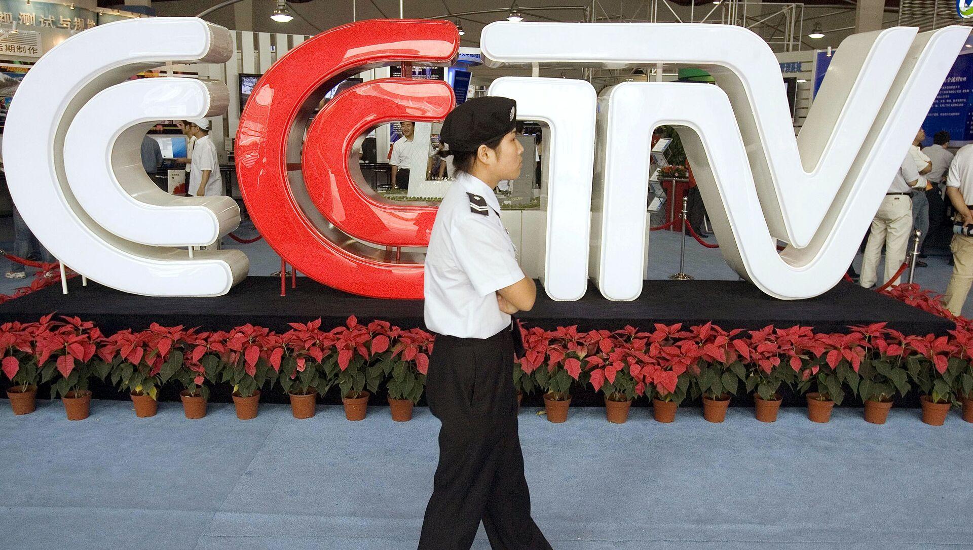 Nhân viên an ninh Trung Quốc đi ngang qua logo của Đài Truyền hình Trung ương Trung Quốc (Tập tin) - Sputnik Việt Nam, 1920, 21.03.2021