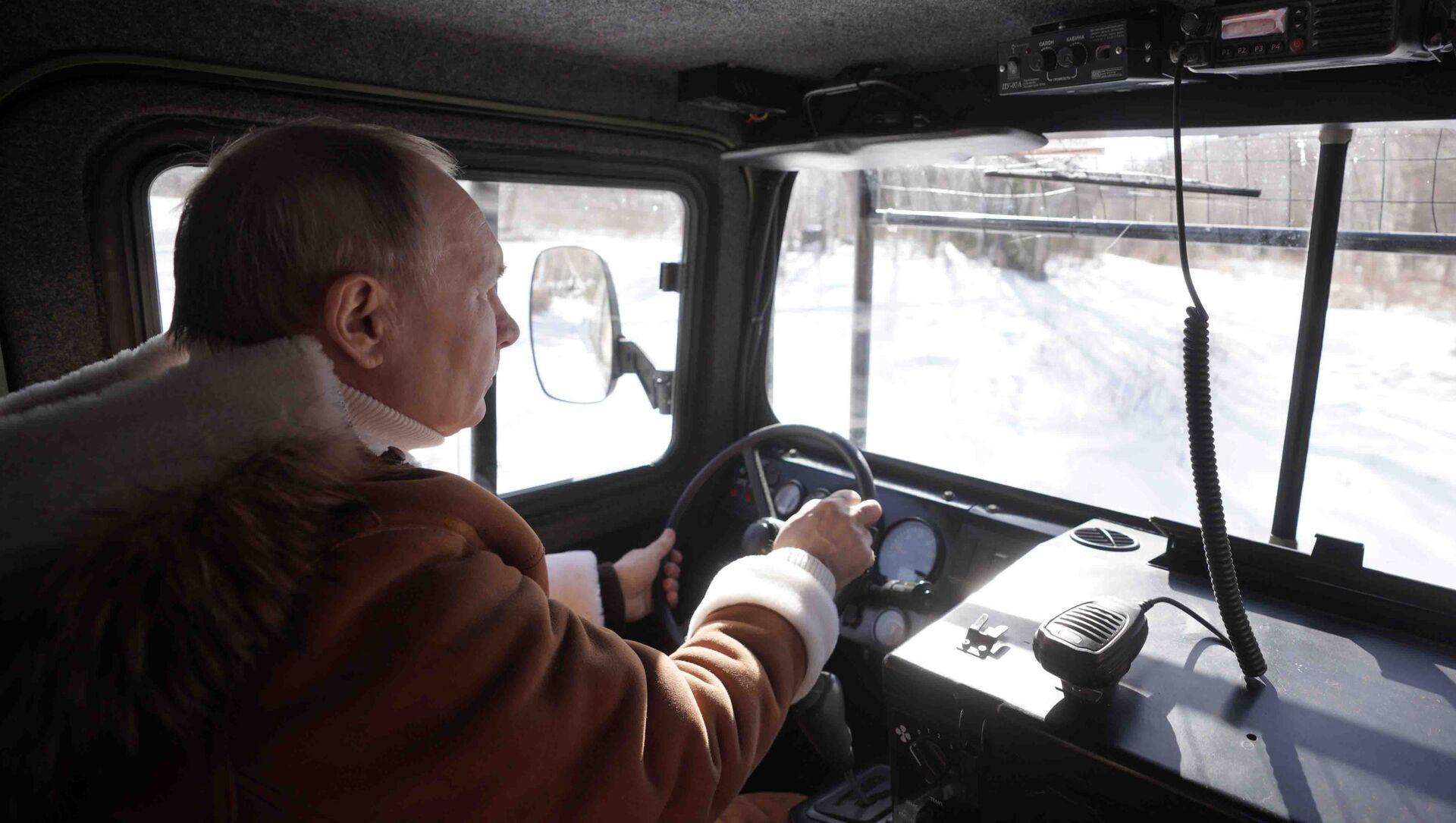 Tổng thống Nga Vladimir Putin lái xe địa hình khi đi dạo trong rừng taiga. - Sputnik Việt Nam, 1920, 22.03.2021