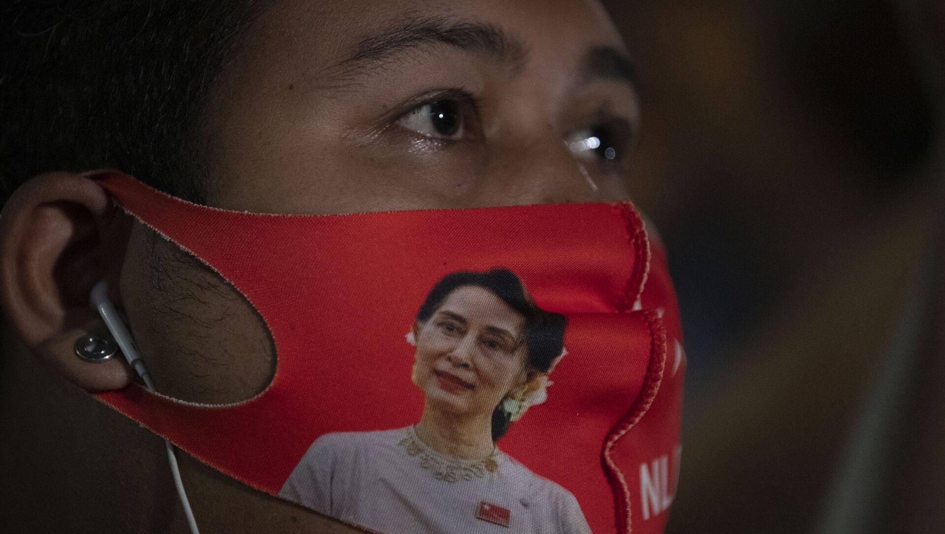 Một công dân Myanmar sống ở Thái Lan đeo khẩu trang có hình nhà lãnh đạo Myanmar Aung San Suu Kyi trong cuộc biểu tình trước Đại sứ quán Myanmar ở Bangkok, Thái Lan, thứ Năm, ngày 4 tháng 2 năm 2021. Quân đội tuyên bố hôm thứ Hai rằng họ sẽ nắm quyền trong một năm, cáo buộc chính phủ của bà Suu Kyi không điều tra các cáo buộc gian lận cử tri trong các cuộc bầu cử gần đây. Đảng của bà Suu Kyi đã quét sạch cuộc bỏ phiếu đó và đảng được quân đội hậu thuẫn đã làm rất kém. Ủy ban Bầu cử tiểu bang đã bác bỏ các cáo buộc. - Sputnik Việt Nam, 1920, 24.03.2021