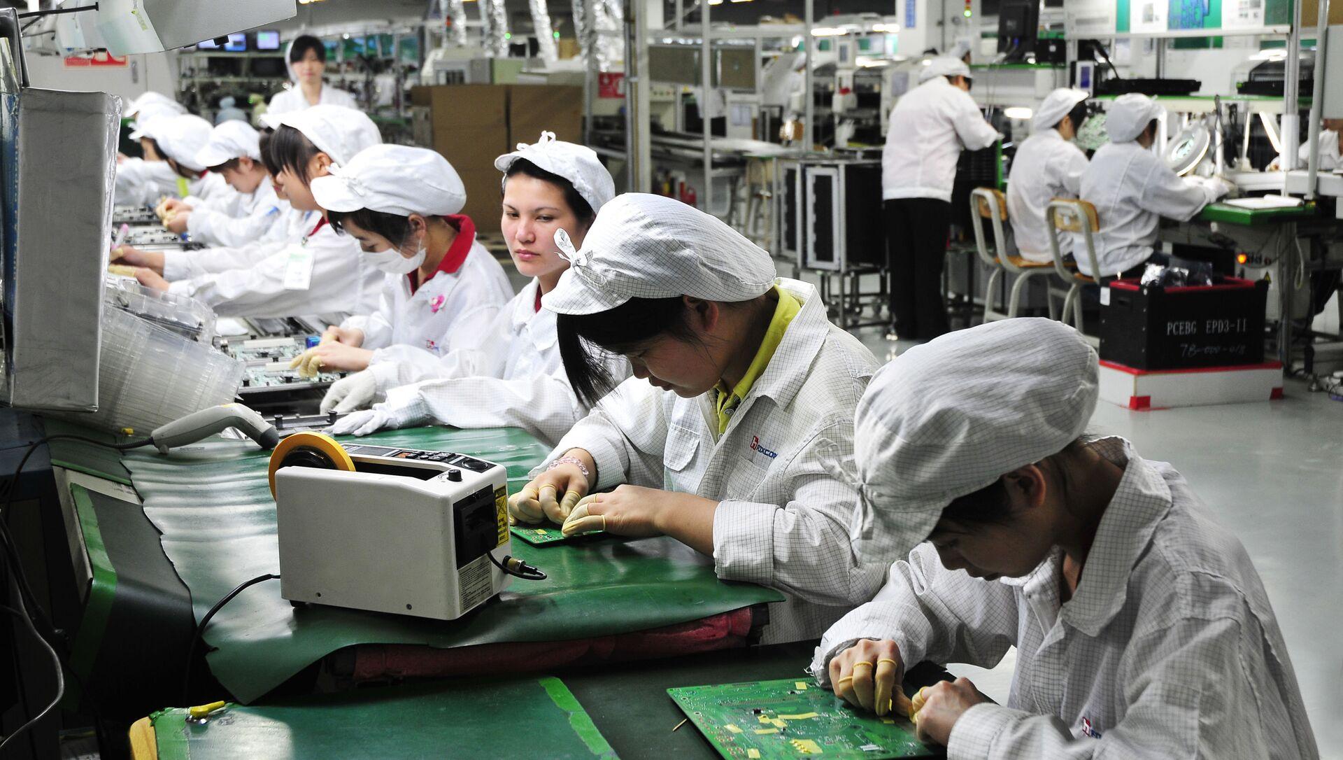 Công nhân làm việc trong phân xưởng của nhà máy Foxconn Technology Group ở Thâm Quyến, Trung Quốc - Sputnik Việt Nam, 1920, 28.05.2021