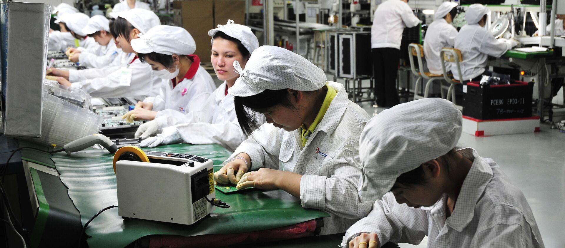 Công nhân làm việc trong phân xưởng của nhà máy Foxconn Technology Group ở Thâm Quyến, Trung Quốc - Sputnik Việt Nam, 1920, 24.03.2021