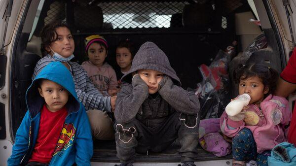 Trẻ em di cư từ Trung Mỹ trên xe Tuần tra Biên giới Hoa Kỳ đang chờ được vận chuyển, Penitas, bang Texas, Hoa Kỳ. - Sputnik Việt Nam