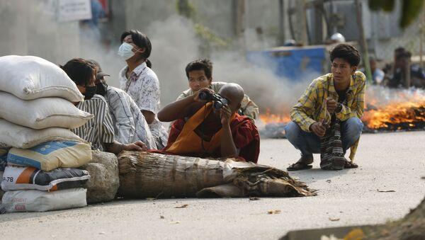 Nhà sư cầm ống nhòm ở sau chướng ngại vật trên đường phố Mandalay, Myanmar - Sputnik Việt Nam