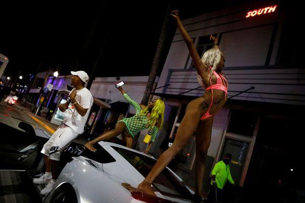 Những người phụ nữ nhảy múa trên nóc ô tô sau giờ giới nghiêm ở bãi biển Miami, Florida - Sputnik Việt Nam