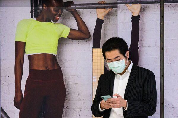 Người đàn ông cầm điện thoại thông minh trước tấm áp phích cô gái ở Hồng Kông - Sputnik Việt Nam