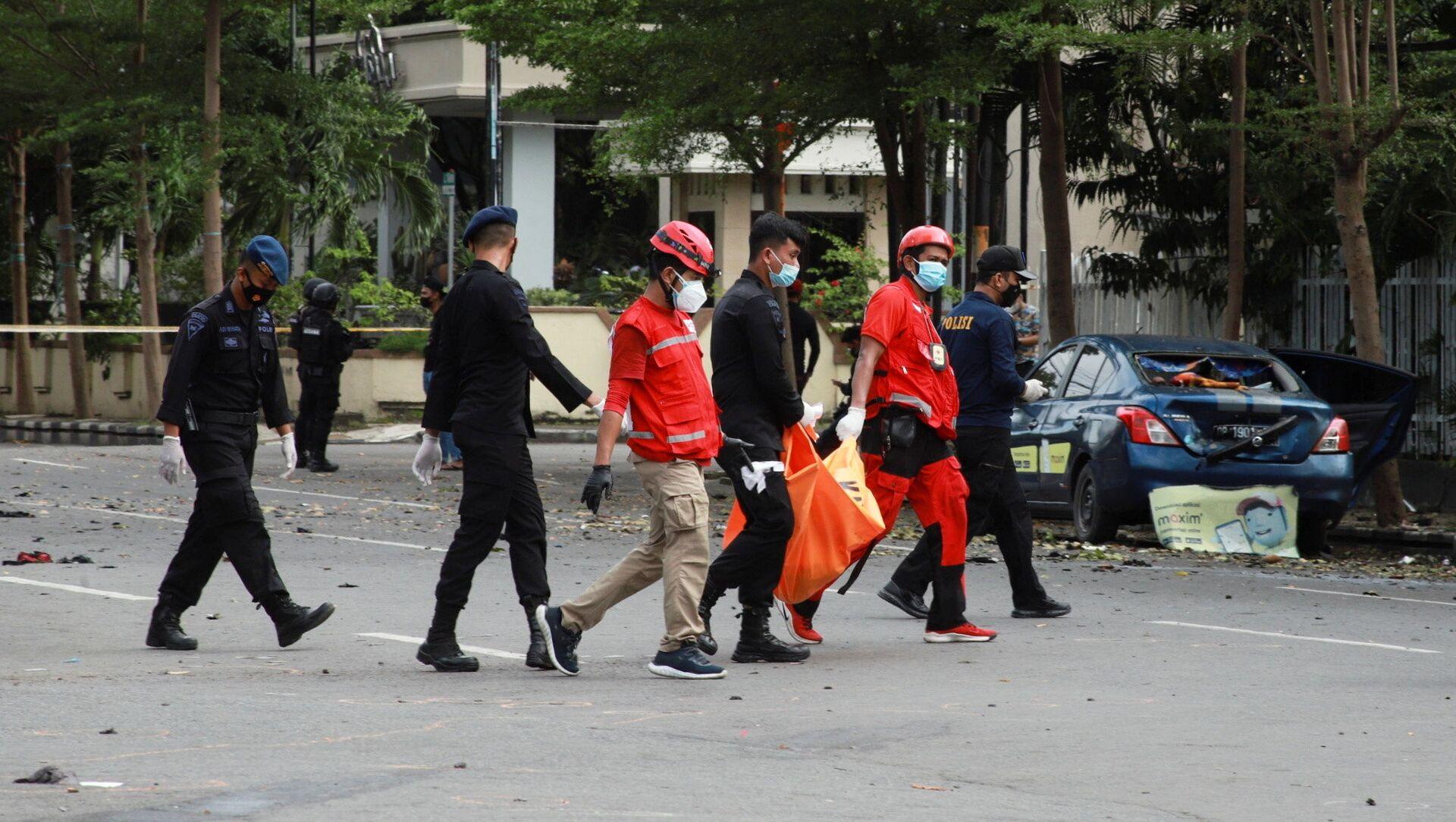 Nhân viên Hội Chữ thập đỏ mang  chiếc túi chứa mảnh di thể nạn nhân của vụ nổ gần nhà thờ Công giáo ở Indonesia - Sputnik Việt Nam, 1920, 29.03.2021