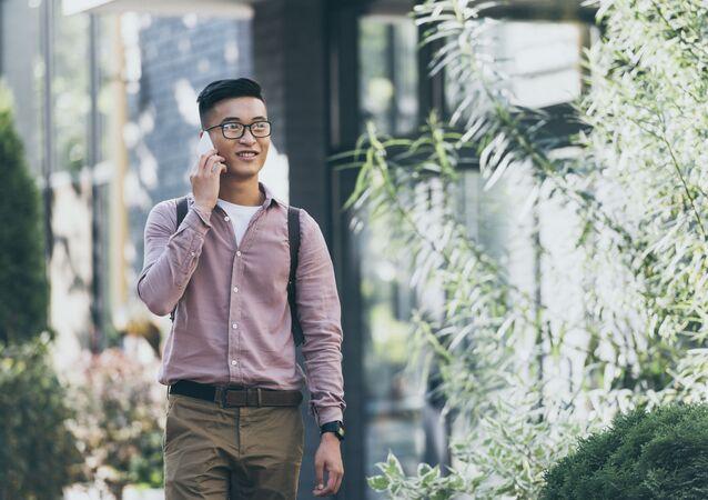 Một thanh niên đang cầm điện thoại trên tay.
