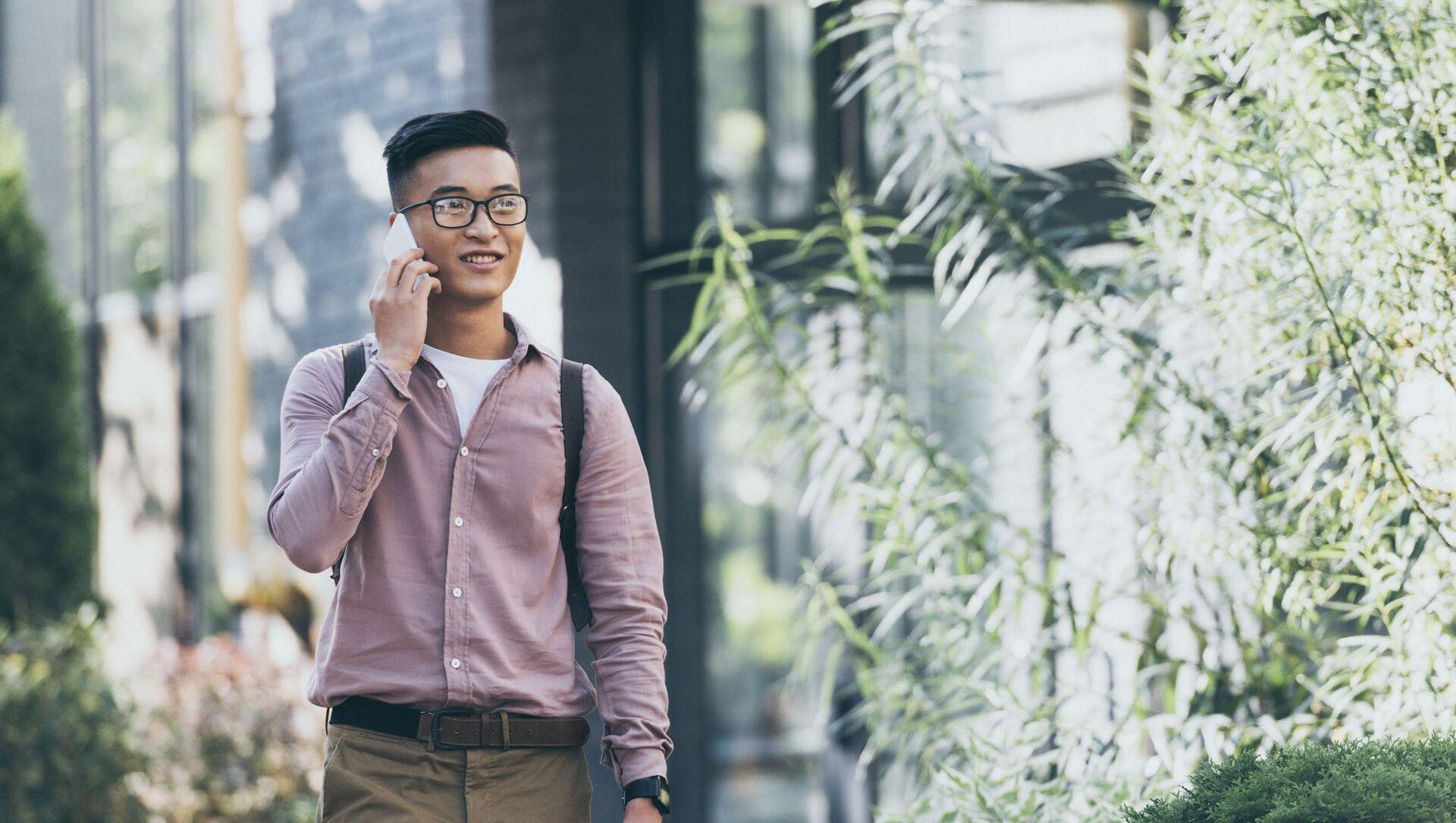 Một thanh niên đang cầm điện thoại trên tay. - Sputnik Việt Nam, 1920, 05.07.2021