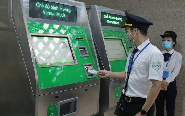 Nhân viên hướng dẫn mua vé tại cây bán vé tự động. - Sputnik Việt Nam
