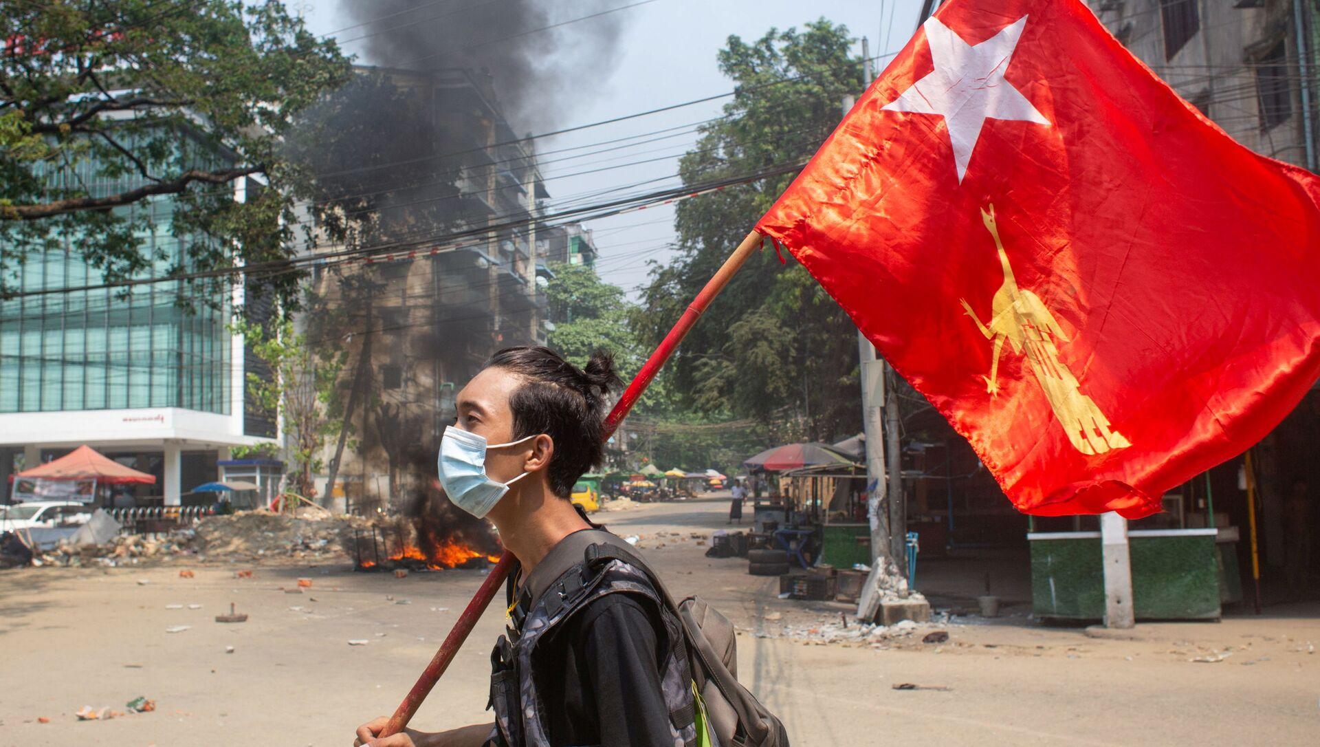 Một người đàn ông cầm cờ của Liên đoàn Quốc gia vì Dân chủ trong cuộc biểu tình phản đối đảo chính quân sự ở Yangon, Myanmar. - Sputnik Việt Nam, 1920, 22.09.2021